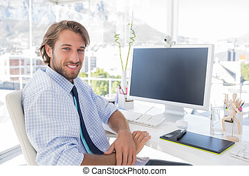 Smiling designer sitting at his desk in bright modern office