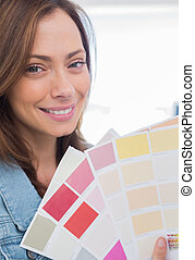 Attractive interior designer holding up colour samples close...
