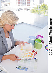 Focus interior designer looking at color charts