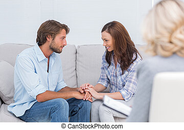 Couple reconciling on the couch while therapist watches