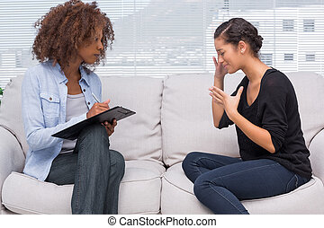 Sad woman speaking to her therapist while she is taking...