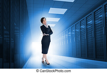 Businesswoman standing in data center and looking thoughtful