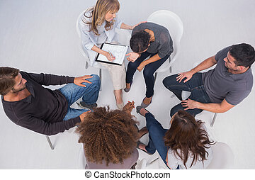Overhead of group therapy session with one woman crying