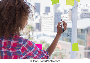 Woman drawing on flowchart wearing check shirt in office