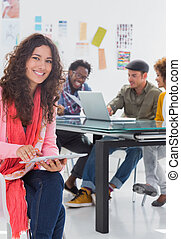 Smiling woman using tablet with creative team working behind...