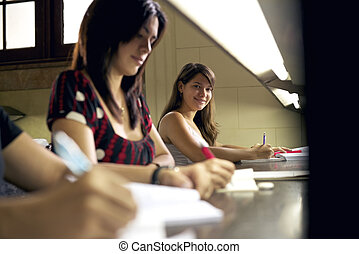 happy female student smiling at camera in college library -...