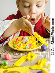 Child playing with spaghetti dish made with plasticine -...