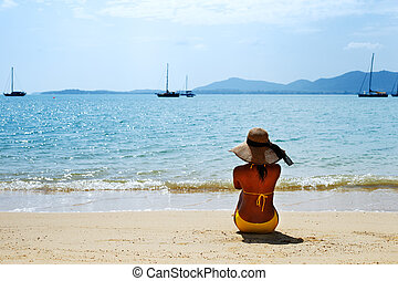 Young woman sun bathing - Young woman in a yellow swimsuit,...