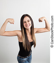 Beautiful young woman flexing her biceps - Beautiful young...