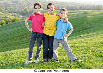 happy kids on the hillside - Group of happy kids standing on...