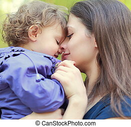 Loving mother holding small happy girl and smiling. Closeup portrait face at face