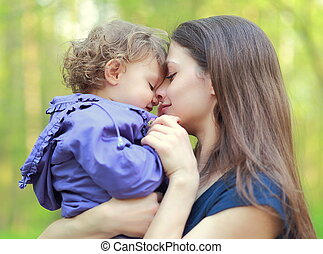 Happy love mother and child girl embracing outdoor summer background. Closeup portrait
