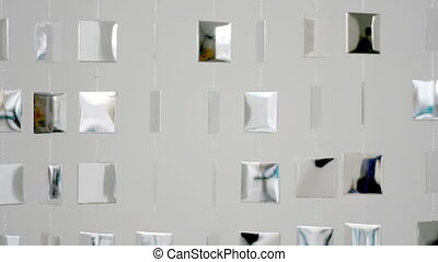 cool metal shapes hanging on wall and moving,with reflection...
