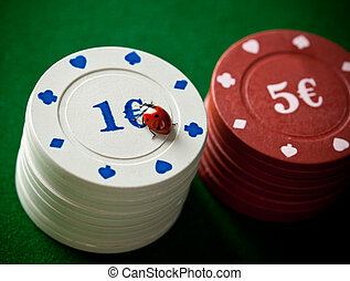 Ladybugs with poker chips on green table