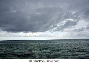 Stormy Cloudy Weather - A ocean water surface under cloudy...