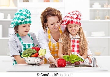 Woman and kids preparing the vegetables for a meal - washing...