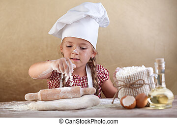 Little girl stretching the cookie dough dispersing some...