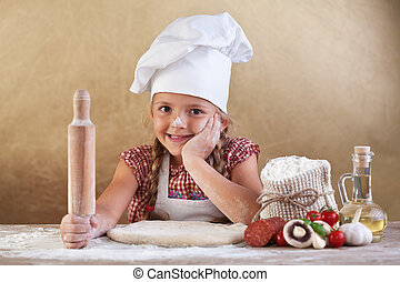 Little girl making pizza - preparing the dough and other...
