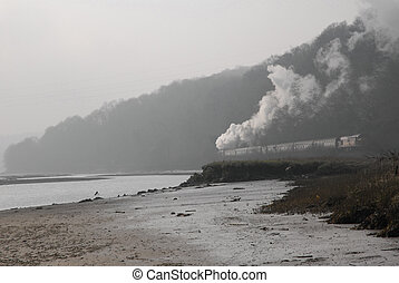 Steam train in mist by estuary Cornwall