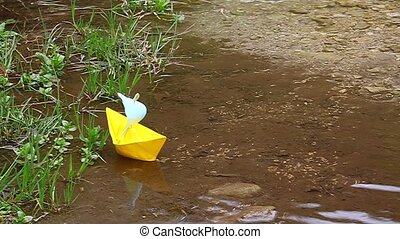 Yellow paper boat floating on the lake