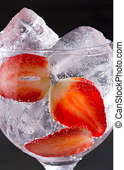 Gin tonic cocktail with strawberries ice macro closeup on...
