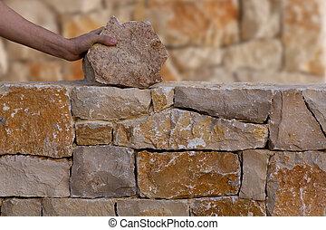 Mason hands working on masonry stone wall stonewall