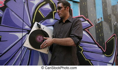 man in urban setting with turntable