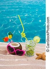 Mojito cocktail on beach sand with coconut and sunglasses