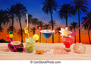 tropical cocktails on white sand mojito on sunset palm trees