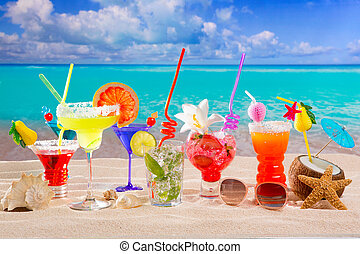 Colorful tropical cocktails at beach on white sand and...