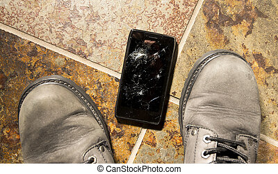 Shattered Smartphone - A smartphone lies broken between the...