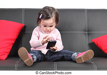 Casual baby sitting on a couch touching a mobile phone -...
