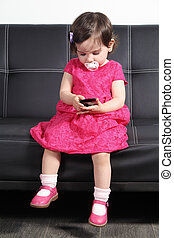 Beautiful baby playing with a smart phone at home -...