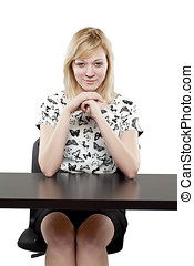 Beautiful blonde woman in business attire looking confident at desk against white background