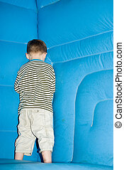 Shy boy - A young boy hides in the corner of a bouncy castle