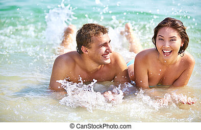 Couple splashing - Young joyful couple lying in water and...