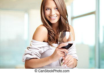 Toast - Young beautiful woman with glass of red wine looking...