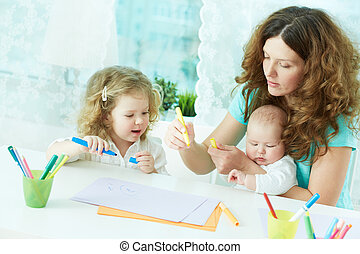 Home recreation - Beautiful mother and her children drawing...