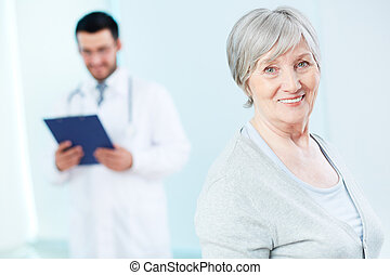 Elderly woman - Senior patient looking at camera with doctor...