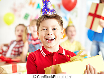 Happy birthday - Joyful boy with giftbox looking at camera...