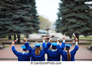 Backs of graduates - Backs of ecstatic students in...