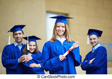 Successful graduate - Friendly students in graduation gowns...