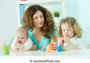Nurture - Pretty woman spending time with her children at...