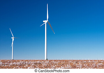 Green energy - Two windmills on a farm against a vibrant...