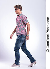 casual man walking forward - side view of a casual young man...