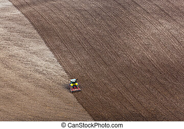 Tractor ploughing a field - A tractor raking a ploughed...