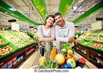 Happy customers - Image of happy couple with cart full of...
