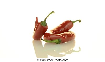 Red chili peppers closeup rotating on white background.