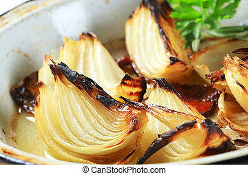 Pan roasted onion wedges on a frying pan