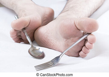 Bad etiquette - Caucasian male feet holding silverware.